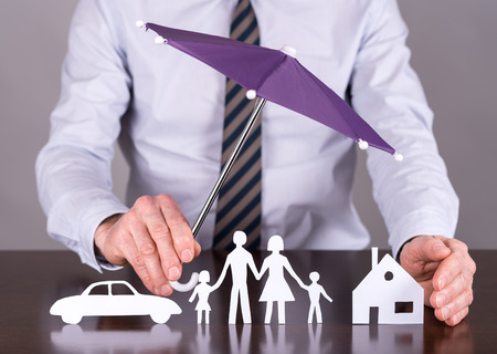 insurer: Man holding an umbrella protecting a family, a house and a car