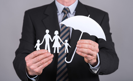 insurer: Man holding an umbrella protecting a family