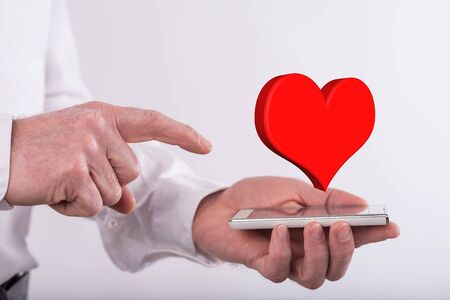 Love concept above a smartphone held by a man Stock Photo