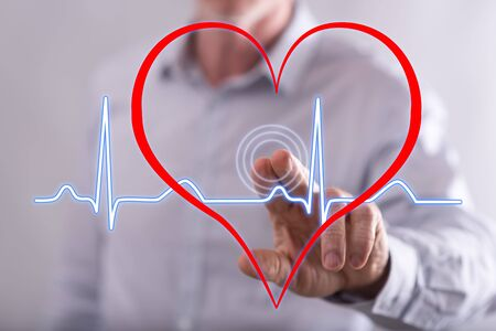 Man touching a heart beats graph on a touch screen with his finger Banco de Imagens - 69228182
