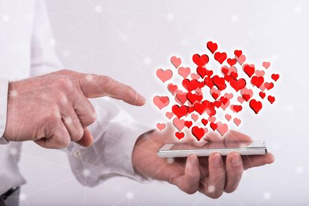 Online dating concept above a smartphone held by a man