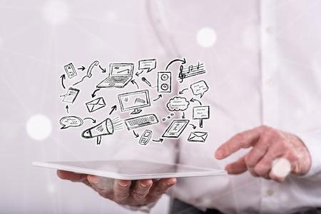 Communicatie concept boven een tablet die door een man op achtergrond wordt gehouden Stockfoto
