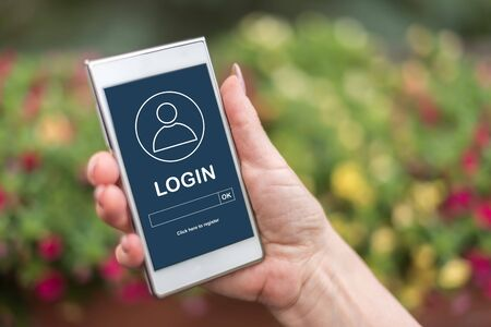 Female hand holding a smartphone with login concept