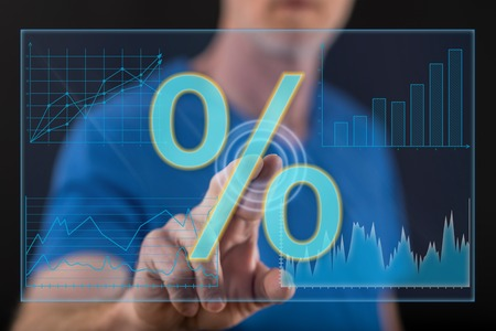 Man touching a digital interest rates datas on a touch screen with his finger Stock Photo