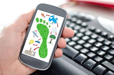 Hand holding a smartphone showing a carbon footprint concept Stock Photo