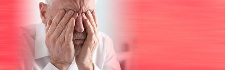 Tired senior businessman rubbing his eyes