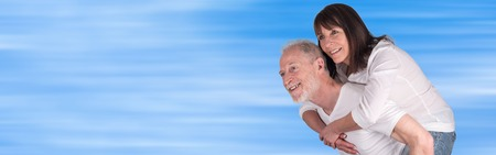 the sixties: Senior man giving piggyback ride to his wife Stock Photo