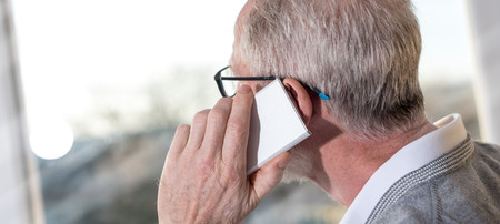 Senior businessman talking on mobile phone and looking through the window Stock Photo