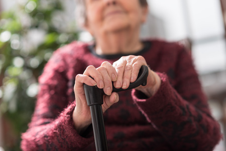 Old woman sitting with her hands on a cane