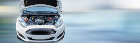 Front of new white car with open motor hood on blurred background