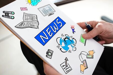 information medium: News concept on a paper held by a hand Stock Photo