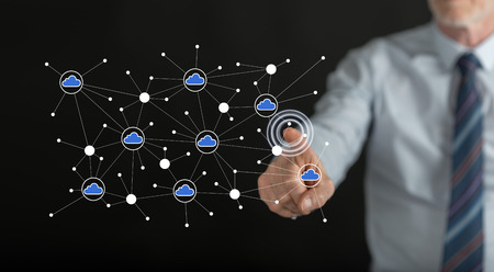 Man touching a cloud networking on a touch screen with his finger Stock Photo