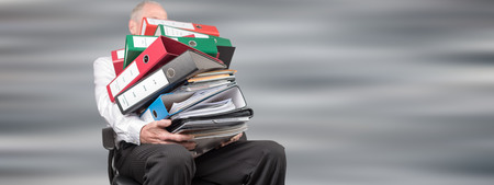 Businessman overworked carrying a pile of binders and folders on grey background