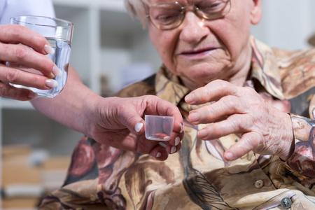 Verpleegster die medicijn geeft aan een oude vrouw