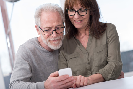 lady on phone: Mature couple using mobile phone at home