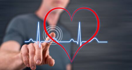 Man touching a heart beats graph on a touch screen with his finger