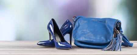Blue handbag and blue high heel shoes on blurred background