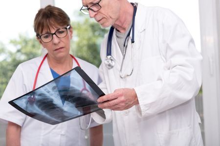 Two doctors examining x-ray report in medical office Stock Photo