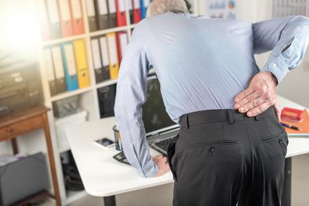 Businessman suffering from back pain in office, light effect Standard-Bild
