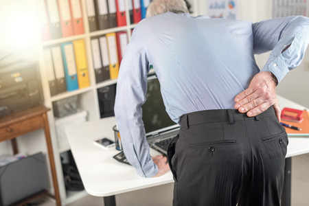 Businessman suffering from back pain in office, light effect Banque d'images