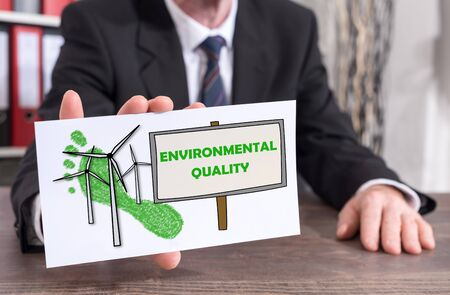 Businessman showing an index card with environmental quality concept
