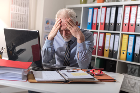 Tired businessman with headache in office Stock Photo