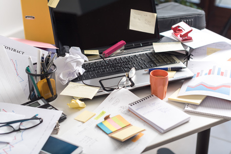 cluttered: Messy and cluttered office desk