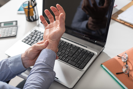 Businessman suffering from wrist pain in office Stok Fotoğraf - 81772327
