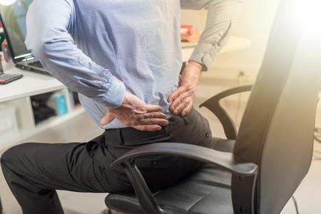 Zakenman die aan rugpijn lijden in bureau, lichteffect