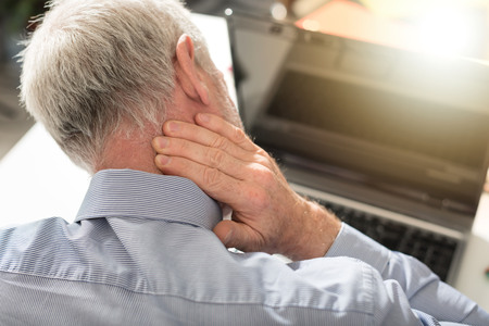 Businessman suffering from neck pain in office, light effect