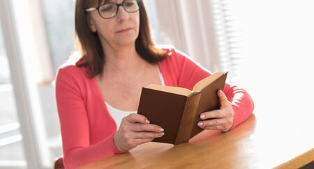 Mature woman reading a book at home