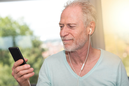 handsfree telephone: Portrait of mature man listening music with earphones at home, light effect