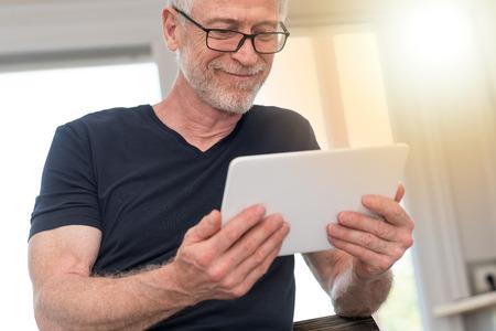 Fälliger Mann, der zu Hause digitale Tablette, Lichteffekt verwendet Standard-Bild - 83358410