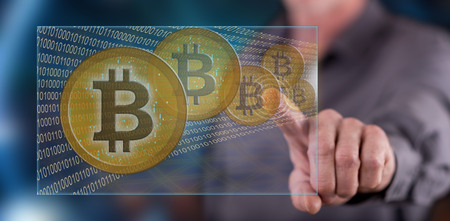 electronic commerce: Man touching a bitcoin currency concept on a touch screen with his finger Stock Photo