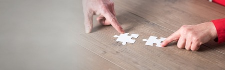 Hands joining two puzzle pieces, teamwork concept Zdjęcie Seryjne
