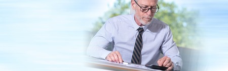 checking account: Senior businessman using a calculator in office Stock Photo