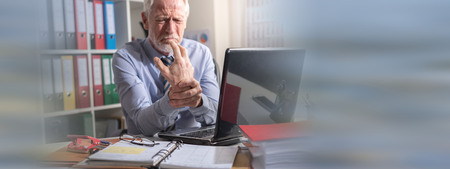 Businessman suffering from wrist pain in office