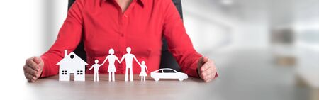 Insurer protecting house, family and car with her hands Standard-Bild