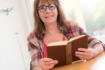 novel: Mature woman reading a book at home