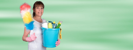 Smiling housewife holding a duster and a bucket with cleaning equipment