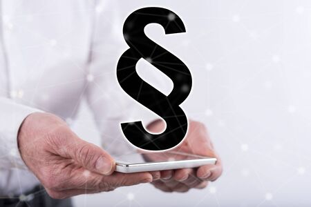 Law concept above a smartphone held by hands