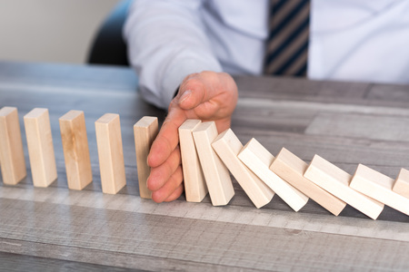 Business control concept by stopping domino effect Stock Photo