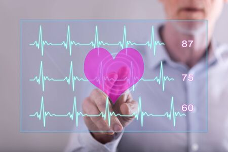Man touching a heart beats graph concept on a touch screen with his finger Banco de Imagens - 86529189