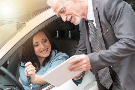 selling service: Car salesman giving informations on tablet to young woman outdoors, light effect Stock Photo