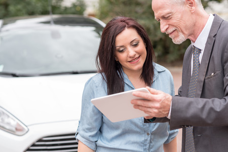 selling service: Car salesman giving informations on tablet to young woman outdoors
