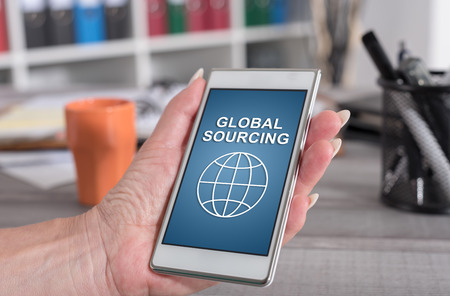 Female hand holding a smartphone with global sourcing concept
