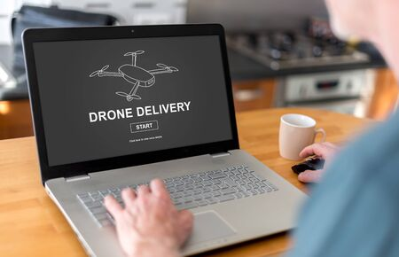 laptop screen: Man using a laptop with drone delivery concept on the screen