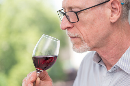 Senior man tasting red wine