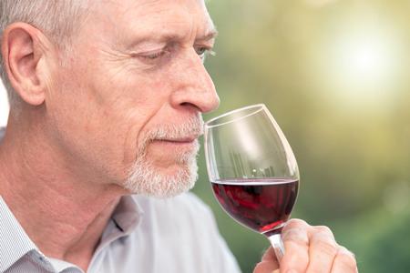 Senior man tasting red wine, light effect