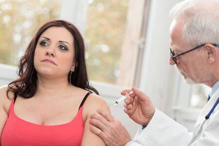 inyeccion intramuscular: Doctor injecting vaccine to attractive young woman Foto de archivo